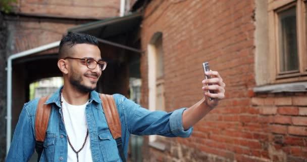 Slow motion of cheerul Arabian man taking selfie with smartphone outdoors