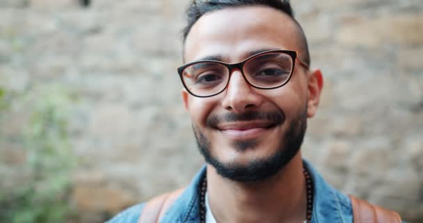 Close-up portrait of good-looking Arabian man in glasses standing outdoors
