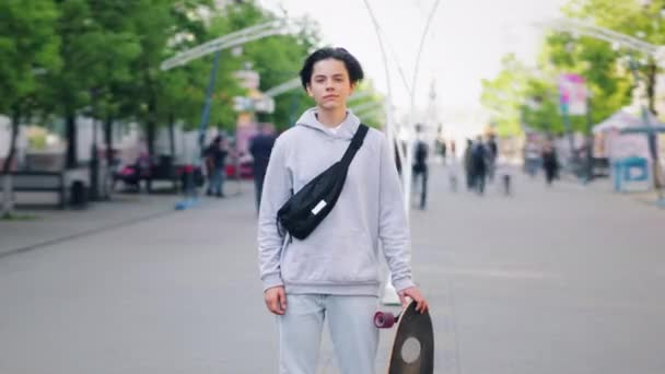 Time lapse of handsome teen standing outside in the street with skateboard