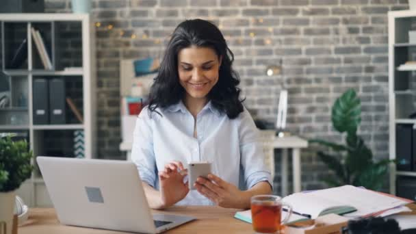 Woman with smartphone enjoying social media at work touching screen smiling
