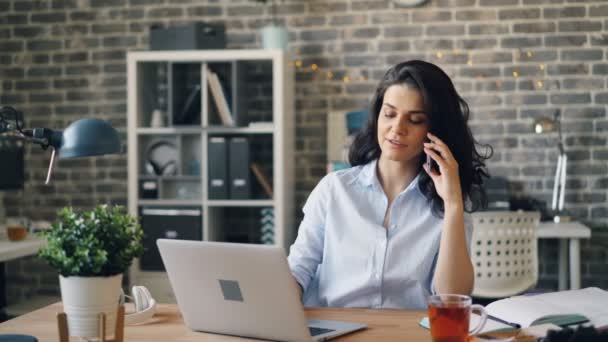 Beautiful businesswoman talking on mobile phone and typing on laptop in office