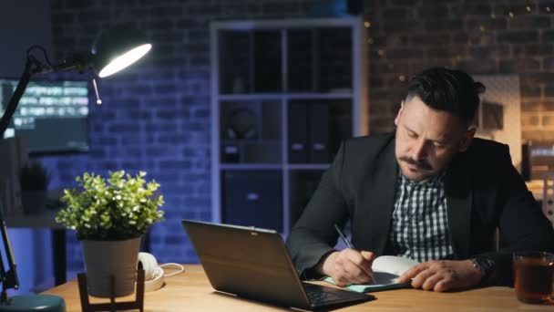 Handsome businessman working with laptop at night in office writing in notebook