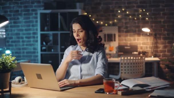 Erschöpfte junge Frau tippt mit Laptop, dann gähnt sie nachts im Büro