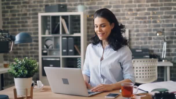 glückliche junge Frau spricht und winkt mit der Hand und blickt auf Laptop-Bildschirm im Büro