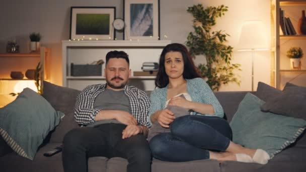 Mladí lidé sledují smutný film v televizi plakat a sedět na pohovce v bytě