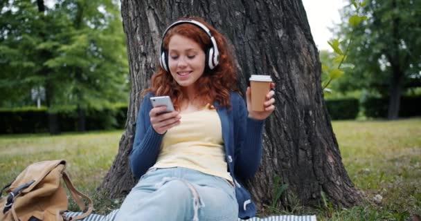 Mosolygó lány hallgat zenét fejhallgató segítségével okostelefon pihentető Park