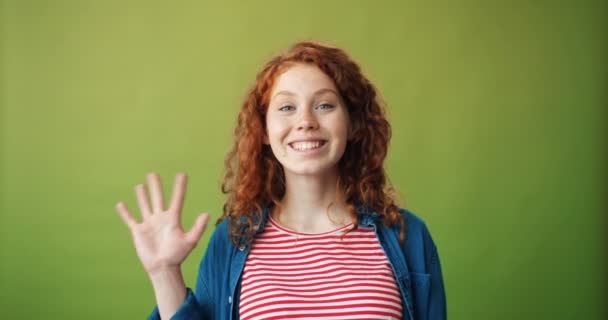 Porträt eines freundlichen Teenagers, der mit der Hand winkt und mit glücklichem Gesicht in die Kamera blickt
