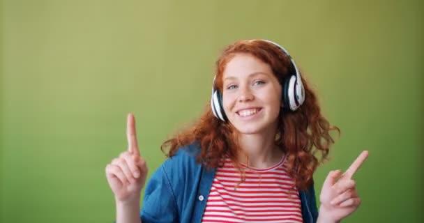 Portrait of teenage girl in headphones enjoying music and dancing