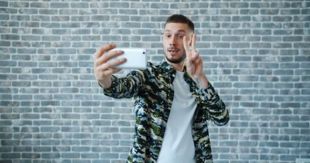Portrait of guy taking selfie with smartphone having fun on brick background