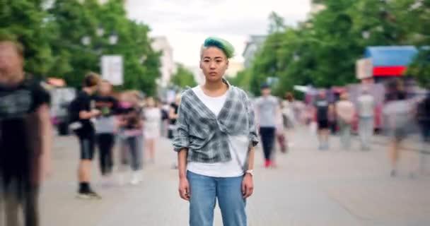 Zoom out idő telik el a stílusos Ázsiai tini állva sétálóutcában egyedül