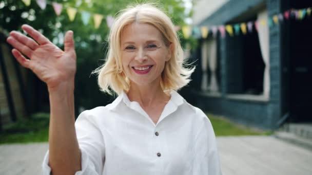Porträt einer attraktiven Frau, die im Freien winkt und lächelt
