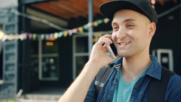 Slow motion portrait of young man speaking on mobile phone in city street