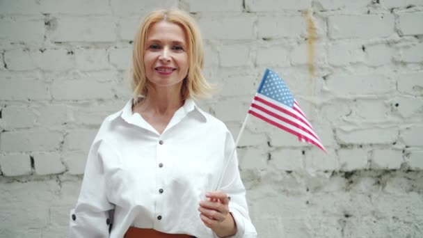 Good-looking American woman holding national US flag smiling on brick background