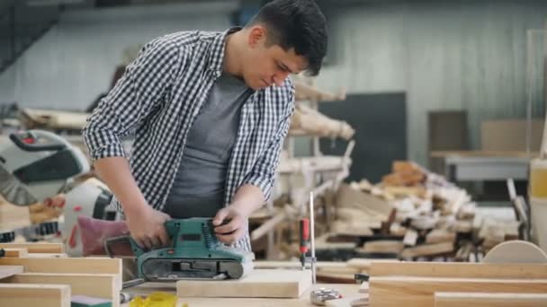 Mladý muž pracující na dřevěné dílně za použití leštícího stroje k polskému dřevě