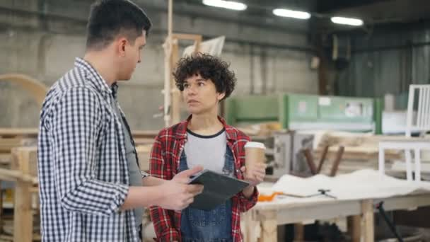 Joyful man and woman chatting in timber workshop holding coffee and tablet