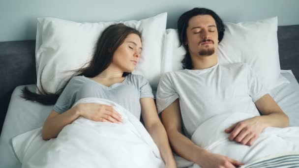 Young attractive man and woman sleeping in bed at home resting together