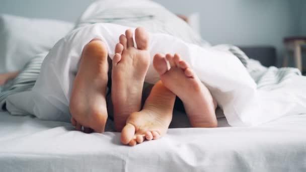 Mans és Womans láb alatt mozgó takaró simogató megható az ágyban