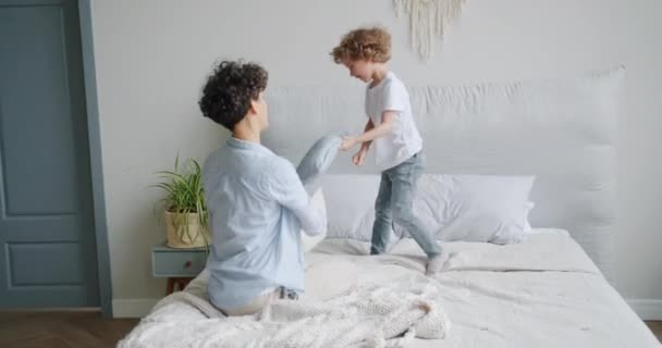 Happy child having fun with mother fighting pillows laughing then falling in bed