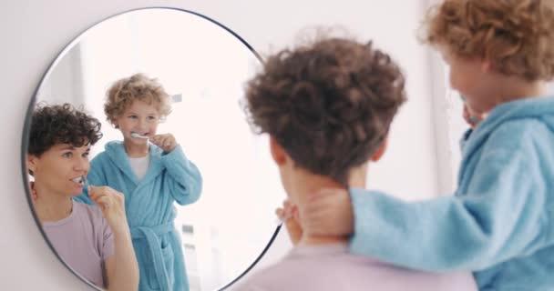 junge Frau und kleiner Junge beim Zähneputzen im Badezimmer