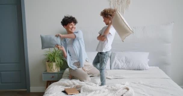 Mladá žena a malý chlapec, kteří si užívají polštář na posteli v bytě