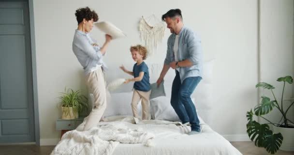 Šťastná rodinná matka, syn otec, bojuje s polštáři doma na posteli se směje