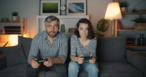 Excited man and woman playing video game in dark apartment having fun
