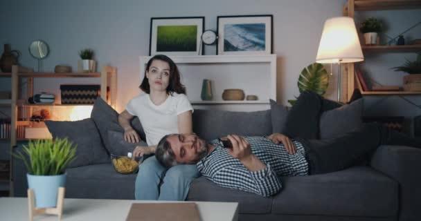 Holka a chlap, co se dívají na televizi v noci a spolu jedí křupky v tmavé místnosti