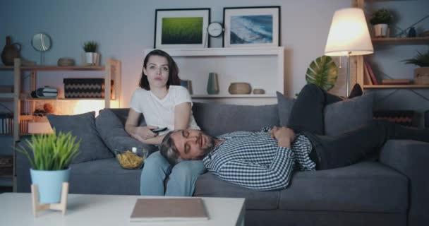 Žena, která se dívá na televizi a v noci spí na gauči