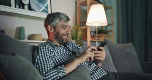 attraktive bärtige Mann genießen Smartphone-Inhalte lachen zu Hause in der Nacht