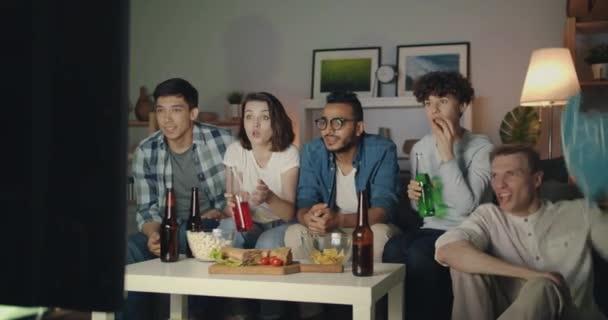 Fröhliche Studenten, die Sport im Fernsehen beobachten, die nachts zu Hause Hoch-Fünf-Meter-Stimmung betreiben