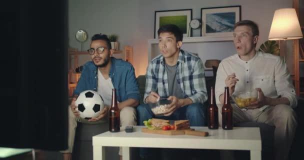 Schöne Jungs beobachten Fußballspiel auf TV essen Snacks feiern Sieg