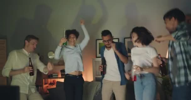 Vzrušené dívky a chlapíci tančící na domácí party s lahvemi s drinky