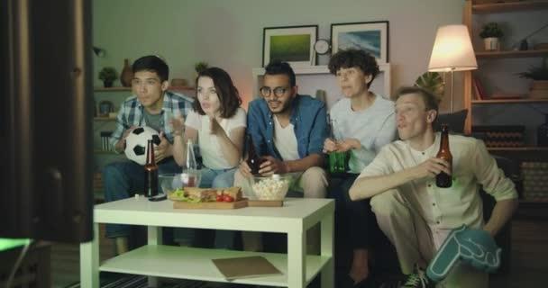Gruppe von Freunden, die Nachts Fußball im Fernsehen schauen, klirrende Flaschen mit Spaß