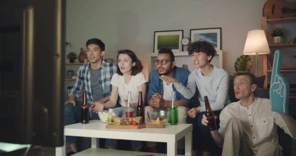 Fröhliche Jugend klirren Flaschen beobachten Sport auf TV in der Nacht jubeln lachen