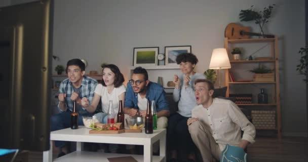 Zeitlupe multiethnischer Gruppe, die nachts im Fernsehen Sport verfolgt und Spaß hat