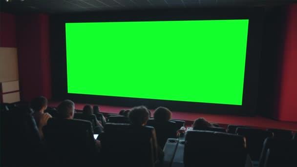 Zuschauer genießen Film auf großer grüner Leinwand im dunklen Kino