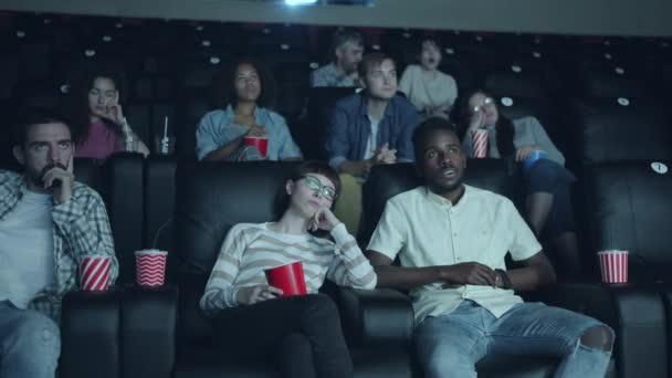 Unhappy viewers yawning in cinema hall watching boring movie together