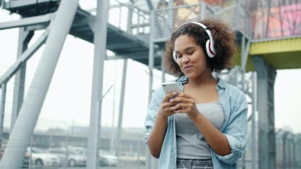 African American woman enjoying music in headphones using smartphone outside