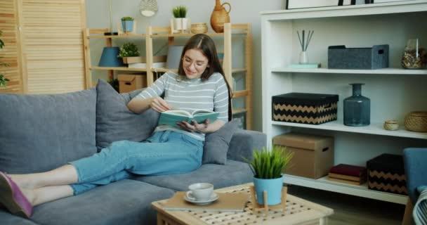 Szép lány olvasás könyv esztergálás oldalak pihentető kanapé a lakásban
