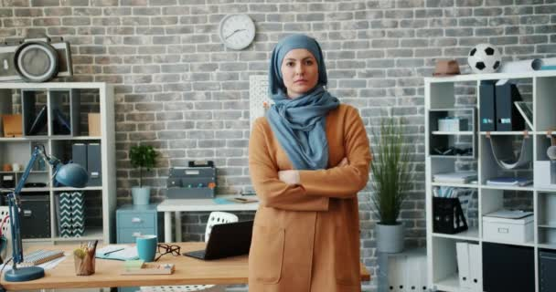 Portrait of ambitious mixed race woman in hijab standing in office arms crossed
