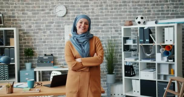 Slow motion portrait of successful Muslim businesswoman smiling in office
