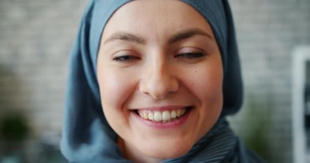 Slow motion close-up portrait of beautiful Muslim girl smiling in office