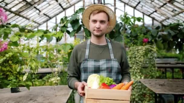 Zeitlupe eines gutaussehenden Mannes in Schürze, der im Treibhaus mit Bio-Lebensmitteln spaziert