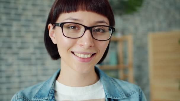 Blízký portrét nádherné mladé Brunetky v brýlích, které se usmívají doma sám