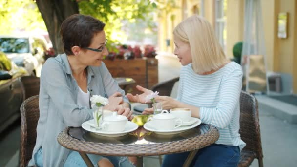 Happy women friends doing high-five and laughing in outdoor cafe in summer
