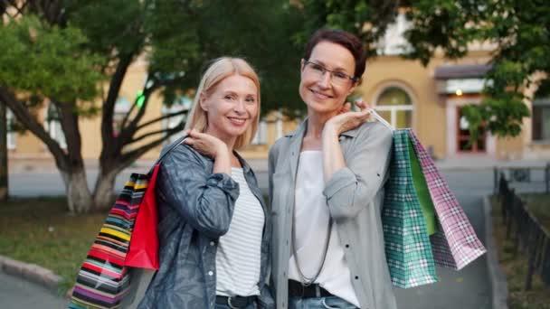 Lassított a csinos nők, fényes bevásárló táskák látszó-on fényképezőgép szabadban