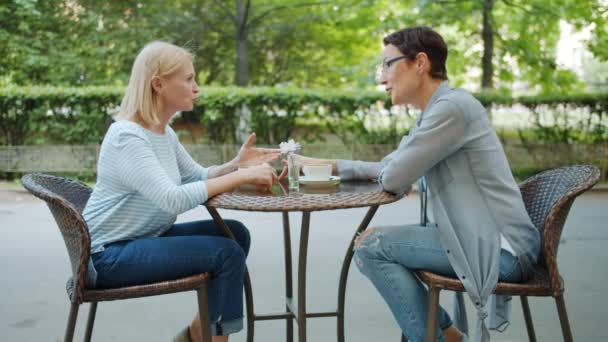 Slow motion of beautiful ladies enjoying conversation in street cafe in summer