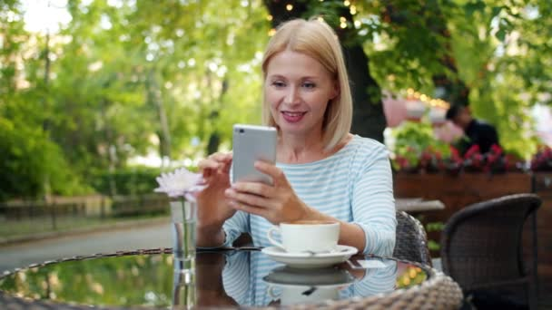 Slow motion of happy woman using smartphone touching screen in outside cafe