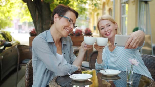 Mature ladies taking selfie with cups in open air cafe holding coffee smiling