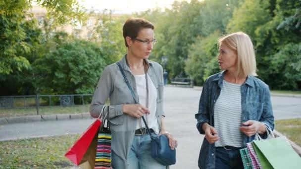 Krásné ženy chodící na ulici s papírovými sáčky, které mluví na podzim